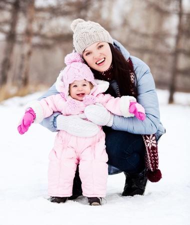 ropa de invierno: feliz madre joven con su hija pasar tiempo al aire libre en el parque de invierno