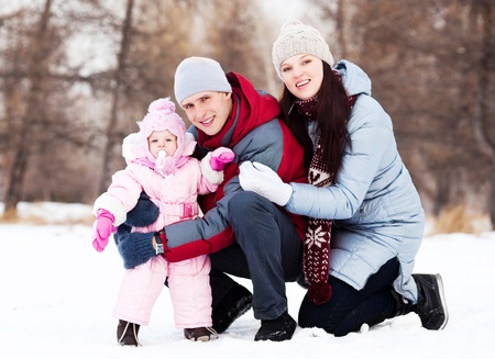 happy young father, mother and their daughter spending time outdoor in the winter park   photo