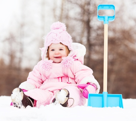 winter day: happy one year old baby girl with a toy spade outdoor on a winter day Stock Photo