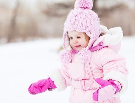bosque con nieve: feliz un a�o de edad ni�a al aire libre en el parque en un d�a de invierno Foto de archivo