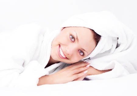 beautiful young woman wearing a towel and a white bathrobe on the bed at home photo