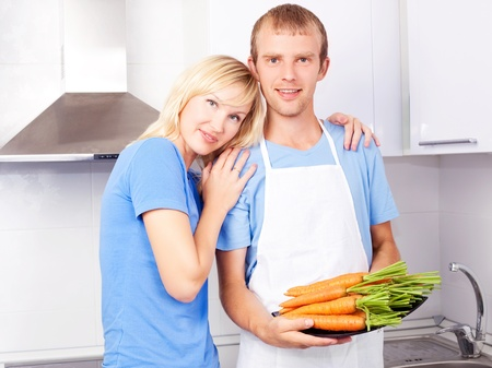 happy young couple cooking together in the kitchen at home photo