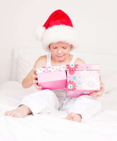 chritmas: little boy celebrating Chritmas and opening presents  on the bed at home