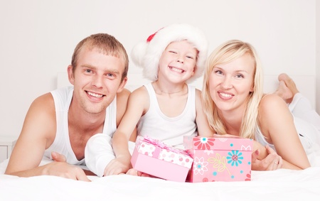 happy family celebrating Chritmas and opening presents, on the bed at home  Stock Photo - 11557116