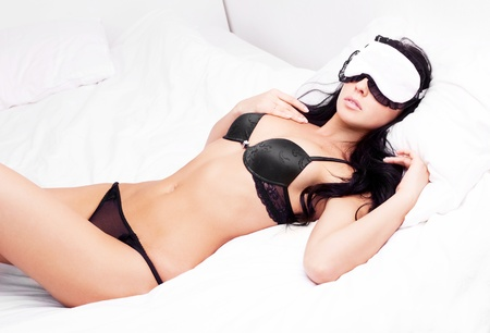 sleep mask: sexy young brunette woman wearing a sleep mask in the bed at home