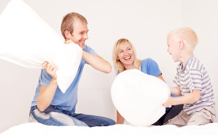 pillow fight: happy family (mother ,father and their son) having a pillow fight in bed at home (focus on the man)