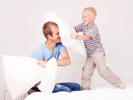 happy laughing father and  son having a pillow fight in bed at home (focus on the man) photo