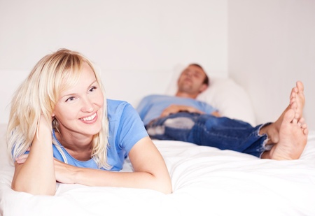 happy young woman and  sleeping man in bed at home (focus on the woman) photo