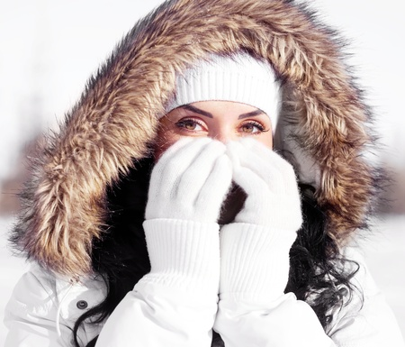 frost: pretty young brunette woman wearing warm winter clothes, covering her face with hands, outdoor in the park