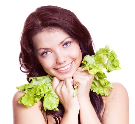 portrait of a young beautiful brunette woman eating salad, isolated against white background photo