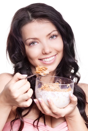 dietary fiber: portrait of a young beautiful brunette woman eating  cornflakes with milk, isolated against white background
