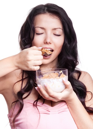 mouth closed: portrait of a young beautiful brunette woman eating  cornflakes with milk, isolated against white background