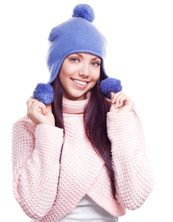 beautiful happy young woman wearing a high neck sweater and a hat with pom-poms, isolated against white background photo