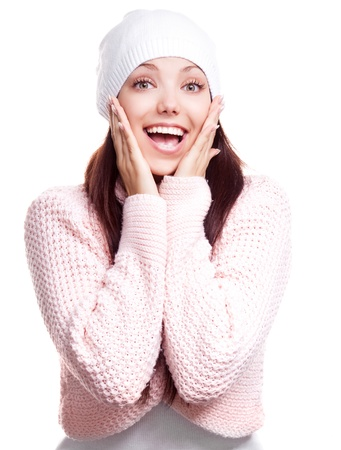 beautiful happy surprised young woman wearing a high neck sweater and a hat, isolated against white background