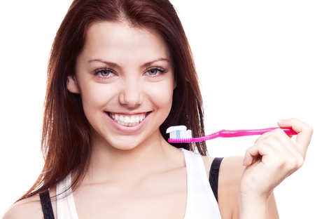 pretty smiling brunette woman brushing teeth, isolated against white background photo
