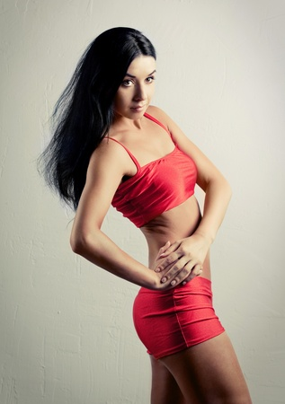studio portrait of a young beautiful sporty woman, wearing red sports shorts and top  photo