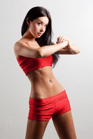 piercing: studio portrait of a young beautiful sporty woman, wearing red sports shorts and top  Stock Photo