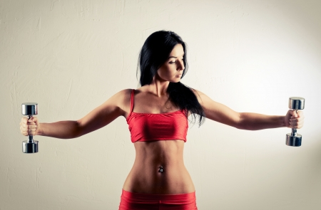 dumbells: studio portarit of a beautiful sporty muscular woman working out with two dumbbells