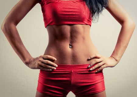 body piercing: belly of a young sporty woman, wearing red sports shorts and top  Stock Photo