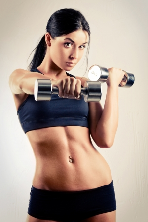 portarit: studio portarit of a beautiful sporty muscular woman working out with two dumbbells