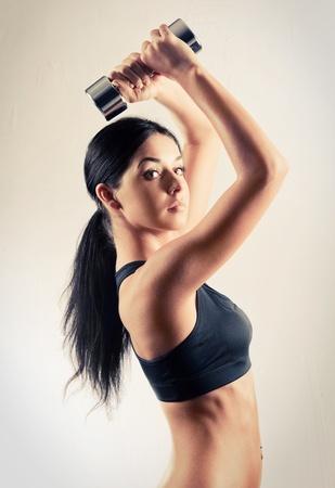 levantamiento de pesas: estudio de portarit de una bella mujer musculosa deportiva de trabajo con dos mancuernas