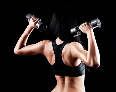 gym: back and hands of a young brunette sporty muscular woman working out with two metal dumbbells, isolated against black background   Stock Photo