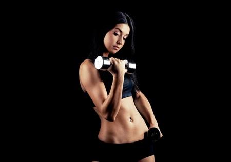 pesas: Retrato de estudio de una hermosa mujer deportivo muscular de trabajo con dos pesas, aislado contra el fondo negro