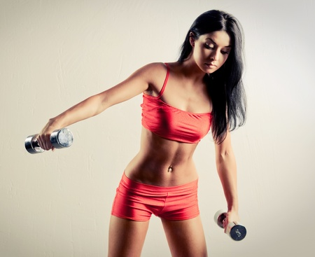 bent: studio portrait of a beautiful sporty muscular woman working out with two dumbbells