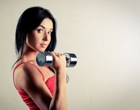 muscle tension tense: studio portrait of a beautiful sporty muscular woman working out with dumbbells