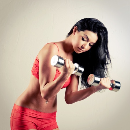 muscle tension: studio portrait of a beautiful sporty muscular woman working out with two dumbbells