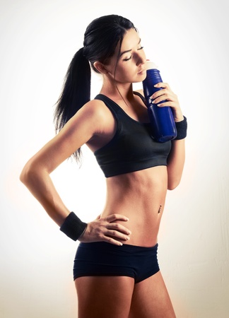 sexy shorts: studio portrait of a young beautiful sporty woman, holding a bottle with water