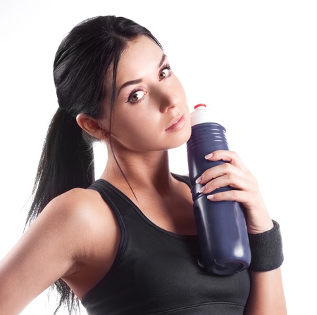 studio portrait of a young beautiful sporty woman, holding a bottle with water photo