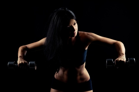 high contrast studio portrait of a beautiful sporty muscular woman working out with two dumbbells, isolated against black background photo