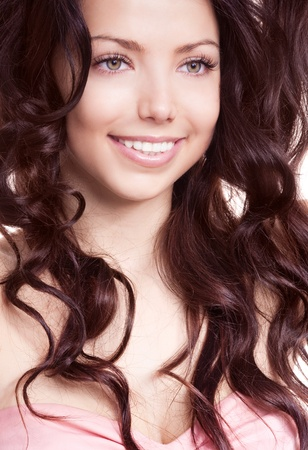 tresses: young beautiful brunette woman with  luxurious long curly hair, isolated against white background Stock Photo