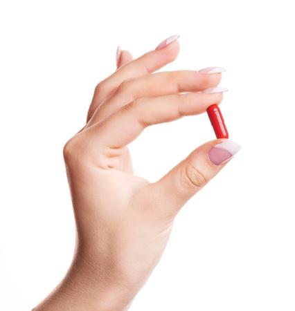 mano de una mujer que sostiene una píldora, aislada contra el fondo blanco
