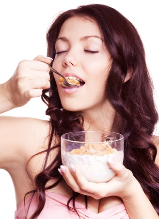 portrait of a young beautiful brunette woman eating  cornflakes with milk, isolated against white background photo