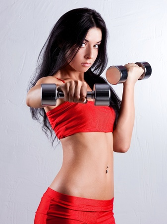 gym girl: studio portrait of a beautiful sporty muscular woman working out with two dumbbells   Stock Photo