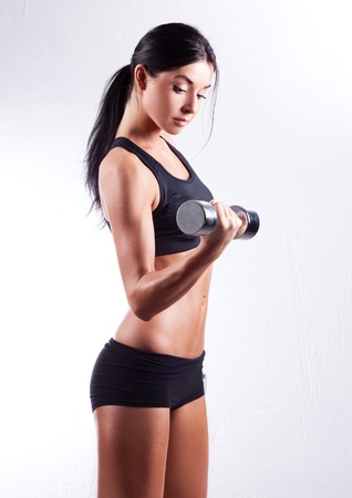 fitness model: studio portrait of a beautiful sporty muscular woman working out with two dumbbells   Stock Photo