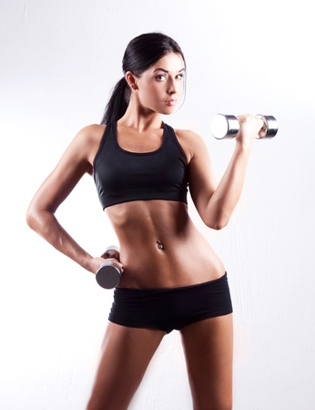 fit girl: studio portrait of a beautiful sporty muscular woman working out with two dumbbells   Stock Photo