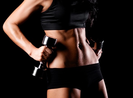weight weightlifting: waist and hands of a beautiful sporty muscular woman working out with two dumbbells, isolated against black background (focus on the belly) Stock Photo