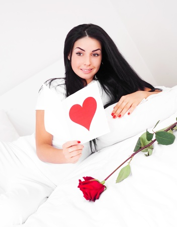 beautiful brunette woman  at home on a Valentines day  reading a Valentines card photo