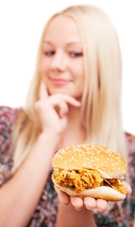 young woman with a hamburger with chicken, isolated against white background (focus on the hamburger) photo