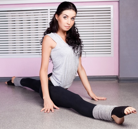 beautiful young  woman sitting on the splits in the gym photo