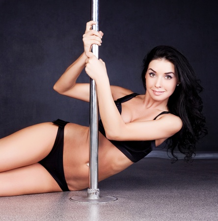 pole dancing: Young sexy pole dance woman against dark background