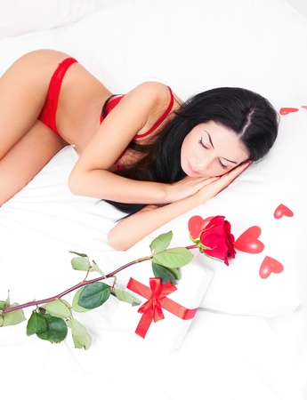 young  sleeping woman with  hearts and a rose on the bed at home photo