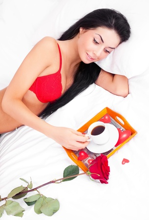 beautiful young brunette woman sleeping in bed at home on a Valentines day with a tray with coffe and a rose standing near her photo