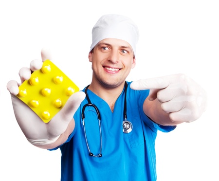 humorous portrait of doctor wearing a  blue uniform, giving us pills and pointing at them, isolated against white background photo