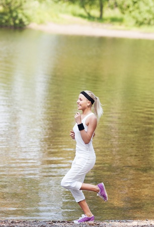 beautiful young  sporty woman running in the park by the pond on a warm summer day   photo
