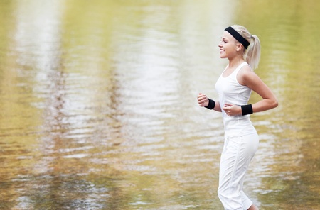 outsides: beautiful young  sporty woman running in the park by the pond on a warm summer day