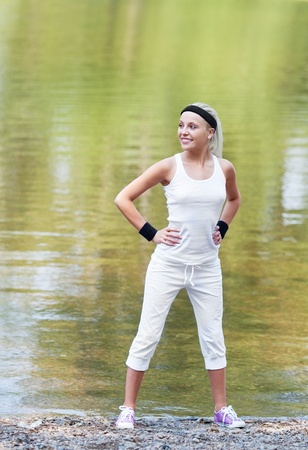 beautiful young  sporty woman jogging in the park by the pond on a warm summer day   photo